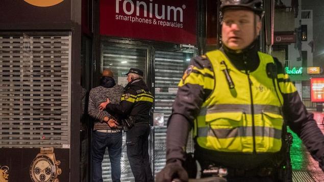 Un policier procède à une arrestation dans une rue, la nuit.