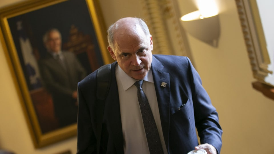 Pierre Fitzgibbon marche, café en main, à l'Assemblée nationale.