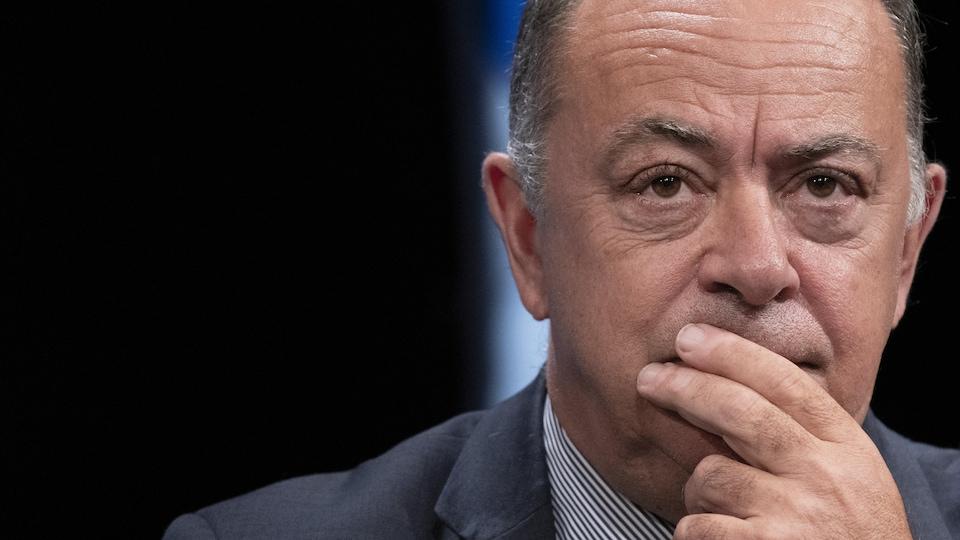 Christian Dubé, l'air pensif et la main sur la bouche, lors d'une conférence de presse.